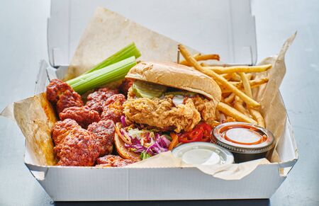 take out box with fried chicken sandwich, boneless wings and french fries