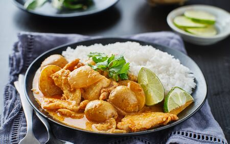 thai massaman curry on plate with jasmine rice and lime wedge