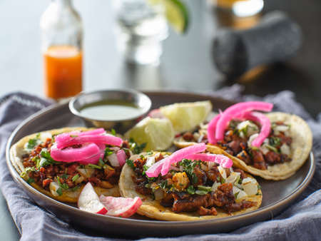 mexican carne asada tacos with pink pickled onions on plate