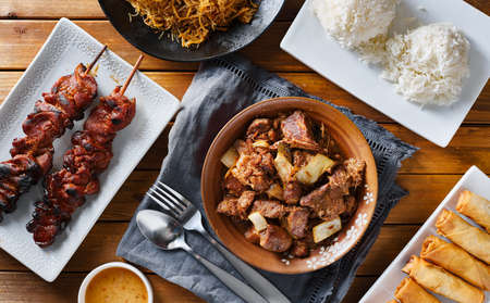 pork adobo meal with filipino foods such as lumpia, pancit noodles, and rice