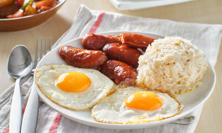 filipino silog breakfast with garlic fried rice, longsilog, and two sunny side up eggs Imagens