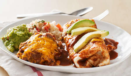 mexican wet burrtio platter with red enchilada sauce, refried beans, rice and gaucamole Stockfoto - 153457328