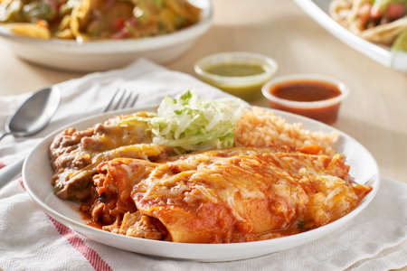 mexican enchilada platter with red sauce, refreied beans and rice Stockfoto