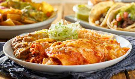 mexican enchilada platter with red sauce, refreied beans and rice Stock Photo