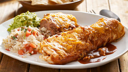 mexican wet burrtio platter with red enchilada sauce, refried beans, rice and gaucamole