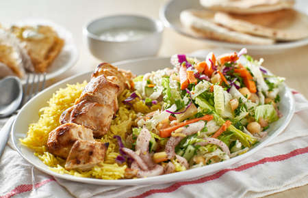 greek chicken souvlaki platter with rice and pickled vegetables