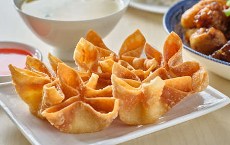 chinese crab rangoon fried wontons on plate with red sauce Stockfoto