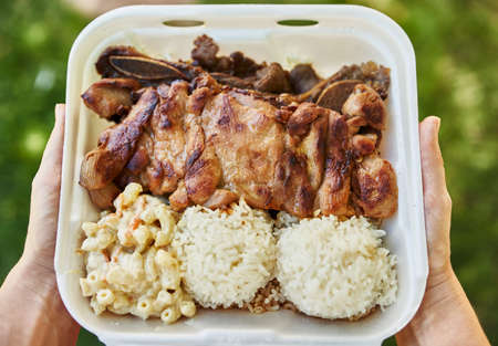 holding open take out container of hawaiian bbq Stockfoto