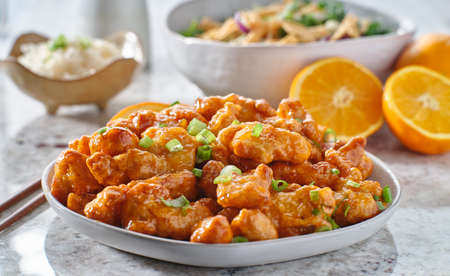 plate of chinese orange chicken with green onion garnish