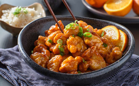 eating bowl of chinese orange chicken with chopsticks Stockfoto