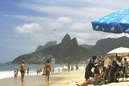 Rio de Janeiro, Brazil. November 17, 2018. Ipanema Beach on the Sunny Summer Day. Hawker walking on beach with beautiful blue sky,