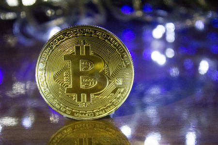 Rio de Janeiro, Brazil - January 16, 2019: Frontal view of golden Bitcoin with bokeh light effect background. Cryptocurrency concept.