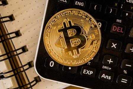 Rio de Janeiro, Brazil - January 16, 2019: Top view stack of golden Bitcoin. Golden bitcoin coin on calculator close up. Editorial