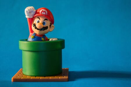 Rio de Janeiro, Brazil. January 30, 2019. Super Mario with pipe toy figure. There are plastic toy sold as part of the McDonald's Happy meals. Isolated on blue background.