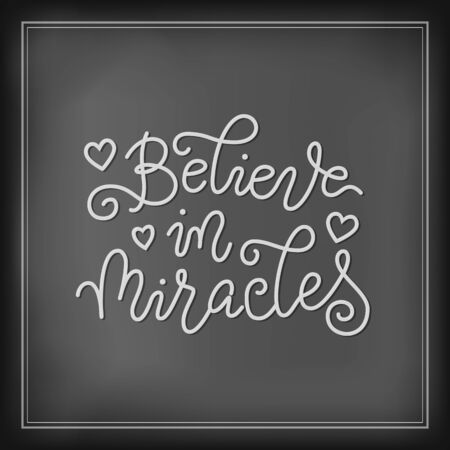Modern calligraphy lettering of Believe in miracles in white with hearts on chalk background