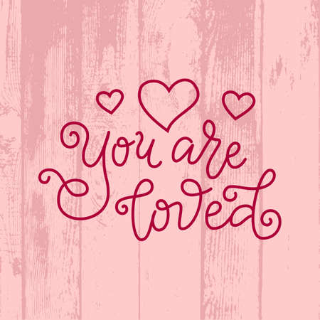 Modern calligraphy lettering of You are loved in red on pink background with wooden texture for decoration, poster, greeting cards, holiday, birthday, postcard, Valentines day, valentine, wedding