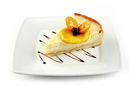 cumquat: Lemon cheesecake with a slice of candy lemon, cumquat and chocolate on white plate