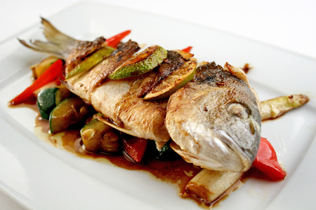 Grilled dorado with slices of lime, sweet pepper, zucchini and the sauce  photo