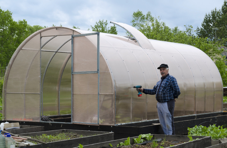 fastens: The man in the country screwdriver fastens to the polycarbonate greenhouse.