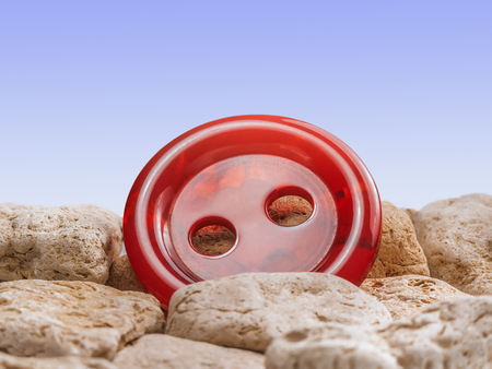 Bright red button among the stones with blue gradient background. Фото со стока