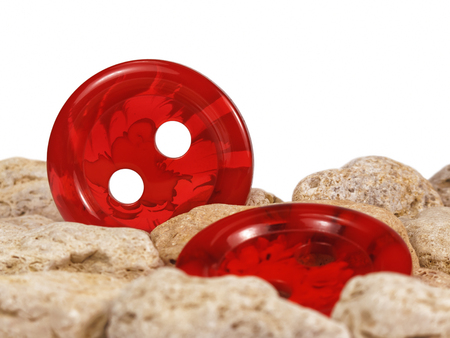 Bright red buttons among stones with white background. Фото со стока