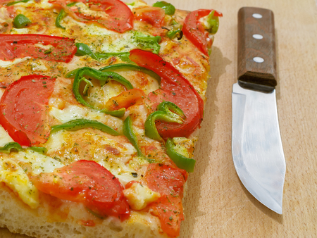 Pizza with tomato and green pepper. Fresh baked piece of pizza and knife on the right.
