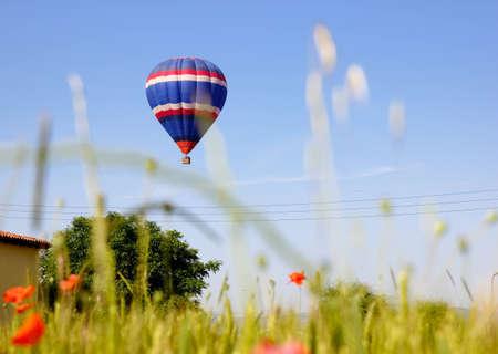 flotating: Hot air balloon landing in a field in Vic, Spain.