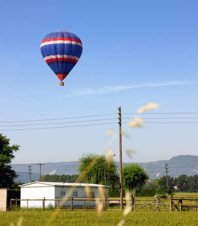 flotating: Hot air balloon landing in a field in Vic, Spain.