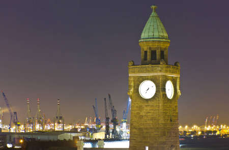 View of the Docks of Hamburg in the evening around the clock tower of the old Elbtunnel in the port facilities photo