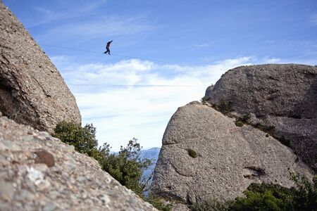 Man practicing highline in Montserrat, Spain. Highline is an equilibrium sport which consists on walking through a rope clamped between two points. photo