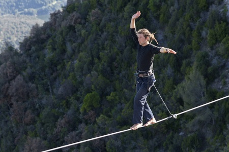 clamped: TAVERTET - APRIL 13: Man practicing highline in Tavertet, Spain on April 13, 2013. Highline is a balance sport that consists walking through a rope clamped between two points and great height below.