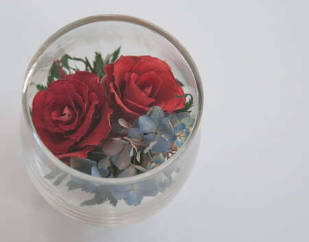 Dried rose flowers in a  sealed clear glass cup photo