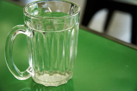 Close up of glass of water on the green table Imagens