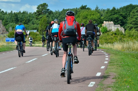A group of cyclists going on the road in the countryside photo