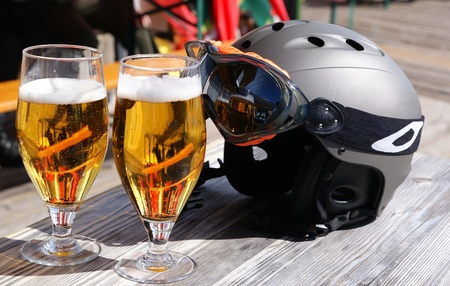 sports bar: Two glasses of beer and a ski helmet on the table