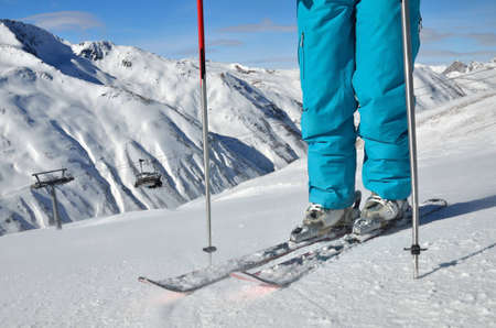 woman s legs in ski boots, standing on skis