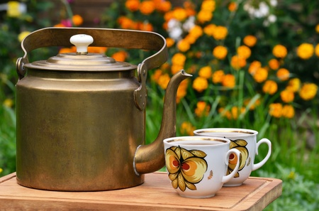 antique brass teapot and two cups on the background of flowers 版權商用圖片