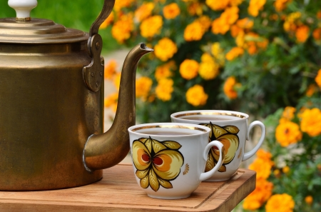 antique brass teapot and two cups on the background of flowers photo