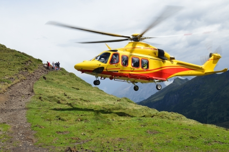 yellow rescue  helicopter in Alps, Val Di Fassa, Italy Editorial