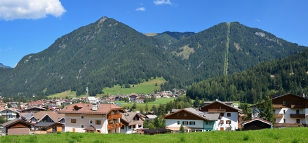fassa: Panoramic view of the alpine village in sunny summer day, Dolomites, Val di Fassa, Italy
