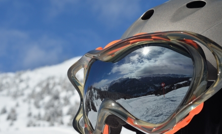 alpine winter landscape with a ski slope is reflected in a ski mask