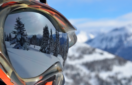 Reflection of the winter mountain landscape in a ski mask