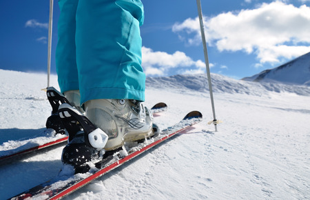 woman s legs in ski boots, standing on alpine skis Stock Photo