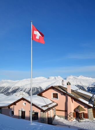 Building with swiss national flag on the alpine skiing resort. St.Moritz, Switzerland