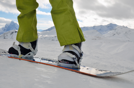 legs standing on a snowboard
