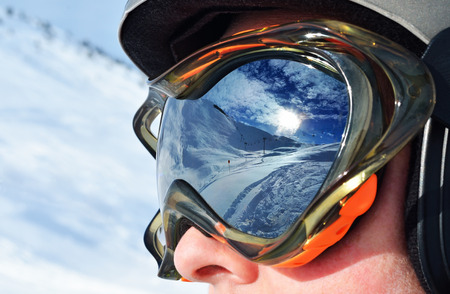 Face of the skier in a ski mask with reflection of the winter mountain landscape. Selective focus 版權商用圖片