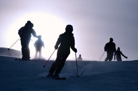 silhouettes of alpine skiers going down the ski slope in contrasting light Stock Photo