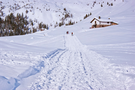 stingy: Walk in the snow towards the mountain lodge in the beautiful winter landscape of the Alps Orobie into resort Cusio, Upper Valley Brembana Stock Photo