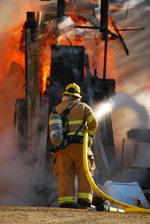 Fire fighter attacking a fully involved shop fire. Stock Photo - 10733991