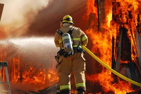 Fire fighter attaccando un incendio del negozio completamente coinvolti. Archivio Fotografico